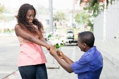 Proof of love. This young men begins to knee with a flower to prove his love to this young  women before him Stock Photo