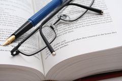 Proof Read. Glasses and pen on big novel royalty free stock images