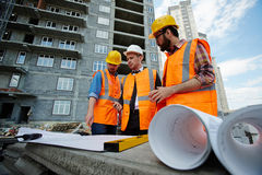 Proofing Construction Blueprints with Supervisor. Low angle portrait of two workmen showing apartment building blueprints to inspector on construction site, all Royalty Free Stock Photography