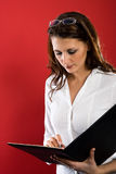 Proofing contract. Nice brownhaired businesswoman with folder in her hands, proofing something Royalty Free Stock Photos