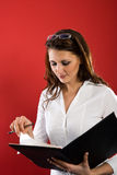 Proofing the rightness. Attractive woman turns in a black folder Stock Photography