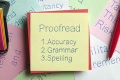 Proofread écrite sur une note Photographie stock libre de droits