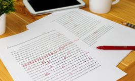 Proofreading paper on table. Hand working on paper for proofreading Stock Photo