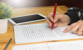 Proofreading paper on table. Hand working on paper for proofreading Stock Images