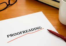 Proofreading word on white sheet with red pen. Books, glasses on wooden table Royalty Free Stock Images