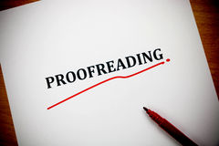 Proofreading word on white sheet with red pen Stock Image