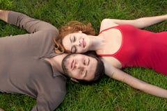 Pares jovenes que duermen en hierba verde Imagen de archivo libre de regalías