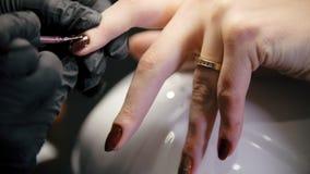 Propósito macro del pulido del clavo - la hembra consigue la manicura profesional en salón de belleza metrajes