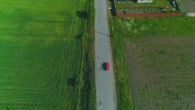 Propósito siguiente superior aéreo de la conducción de automóviles roja a lo largo del camino del campo 4K almacen de metraje de vídeo