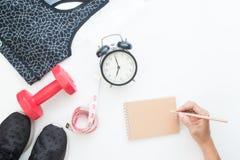 Propósito superior de resolver concepto con la mano de la mujer que sostiene el lápiz con el cuaderno, equipos de deporte y el de Foto de archivo