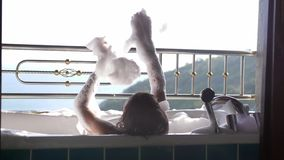 Propósito trasero de bañar a la mujer joven que se relaja en la bañera de aumento de la espuma La muchacha goza del balneario en  almacen de video