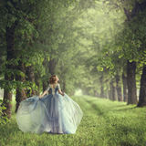 Propósito trasero de colocar a la mujer rubia hermosa joven en vestido azul Imagen de archivo