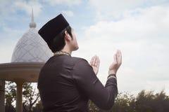 Propósito trasero del aumento musulmán asiático del hombre ambo su mano a rogar Imagen de archivo libre de regalías