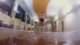 Propósito trasero del salto del hombre en piscina y de nadar la braza metrajes