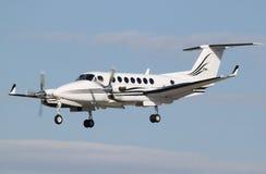 Prop plane landing. A small white prop plane landing Royalty Free Stock Image