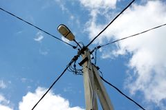 Prop of power supply line over blue sky with white clouds Stock Image