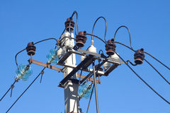 Prop top of power supply line over blue cloudless sky. Closeup Royalty Free Stock Photos
