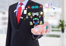 Propagação da mão do homem de negócios com dos ícones da aplicação que vêm acima dele no escritório (borrado) Imagens de Stock Royalty Free
