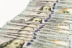Propagação de muitas cédulas de cem dólares na superfície do branco Fotografia de Stock Royalty Free