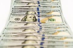 Propagação de muitas cédulas de cem dólares na superfície do branco Imagem de Stock Royalty Free