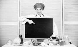 Propaganda real Cozinheiro principal que apresenta algo em cozinhar a escola Mulher bonita que aponta o dedo no quadro-negro vazi foto de stock