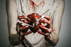 Propaganda social e a luta contra a toxicodependência: as mãos ensanguentados dedicam-se guardar a seringa e o coração humano ens fotos de stock