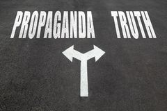 Propaganda vs truth choice concept. Two direction arrows on asphalt Royalty Free Stock Images