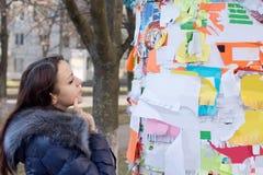 Propagandas pensativas da leitura da mulher em uma placa fotos de stock royalty free