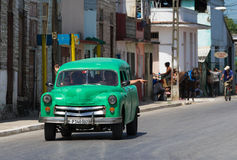 Propelled green classic car on the road in Cuba Stock Images