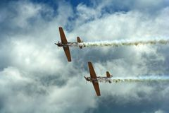 Propeller aircrafts during air show. Propeller aircrafts with white smoke trails during air show Stock Images