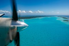 Propeller airplane detail flying in tropical paradise Royalty Free Stock Images