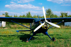 Propeller of the blue airplane on the grass of airfield Royalty Free Stock Images