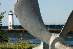 Propeller and Lighthouse. LIghthouse at Manistee, Michigan, framed by blades of old ship propeller Stock Photo