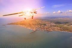 Propeller plane flying over coastal of towkn sun light behind stock photo