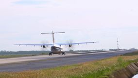 Propeller, twin-engine aircraft rolls on the runway. Day. Airfield Phuket International Airport. Slow Mottion. Propeller, twin-engine aircraft rolls on the stock footage