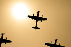Propellor fighter Airplane silhouettes and sun. Propellor fighter Airplane silhouettes armed with bombs Royalty Free Stock Image