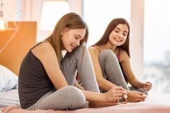 Pleasant teenage girls applying nail polish Royalty Free Stock Images