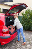 Proper lifting heavy boxes. A young woman lifts a crate of bottles from their car. real life prevents back pain and herniated disc Royalty Free Stock Photos