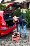 Proper lifting heavy boxes. A young woman lifts a crate of bottles from their car. real life prevents back pain and herniated disc Royalty Free Stock Images