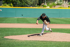 Proper mechanics of pitching. Mens` baseball pitcher throwing the curveball with maximum spin Royalty Free Stock Image