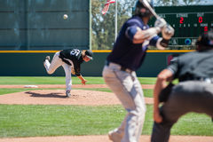 Proper mechanics of pitching. Mens` baseball pitcher throwing the curveball to the batter Royalty Free Stock Photos