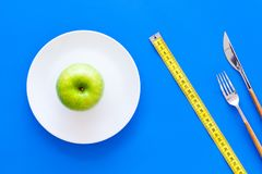 Proper nutrition with dietary fibre for weight loss. Apple on plate near measuring tape on blue background top view.  stock photography