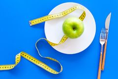 Proper nutrition with dietary fibre for weight loss. Apple on plate near measuring tape on blue background top view.  stock image