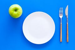 Proper nutrition with dietary fibre for weight loss. Apple on plate near measuring tape on blue background top view.  royalty free stock image