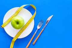 Proper nutrition with dietary fibre for weight loss. Apple on plate near measuring tape on blue background top view copy. Proper nutrition with dietary fibre for royalty free stock image