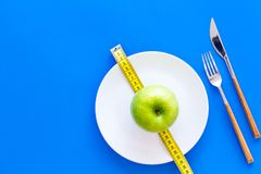 Proper nutrition with dietary fibre for weight loss. Apple on plate near measuring tape on blue background top view copy. Proper nutrition with dietary fibre for royalty free stock images
