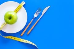 Proper nutrition with dietary fibre for weight loss. Apple on plate near measuring tape on blue background top view copy. Proper nutrition with dietary fibre for stock image