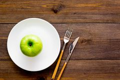 Proper nutrition with dietary fibre for weight loss. Apple on plate near measuring tape on dark wooden background top. View royalty free stock photos