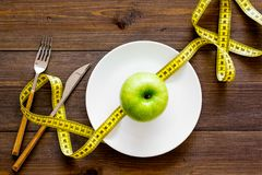 Proper nutrition with dietary fibre for weight loss. Apple on plate near measuring tape on dark wooden background top. View stock image