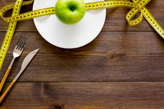 Proper nutrition with dietary fibre for weight loss. Apple on plate near measuring tape on dark wooden background top. View royalty free stock image